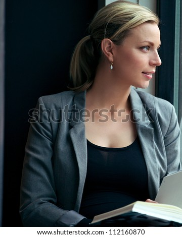 Beautiful woman reading a book has become distracted and is looking out to her left lost in thought - stock photo