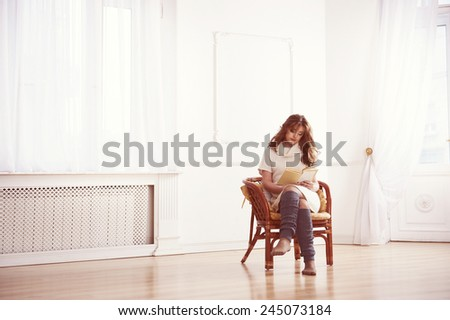 Beautiful woman reading a book in living room. Instagram toning. - stock photo