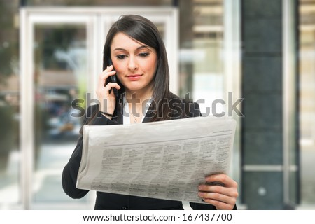 Beautiful woman reading a newspaper - stock photo