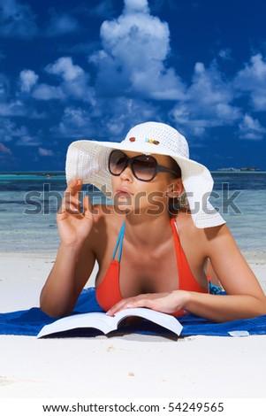 Beautiful woman reading book near water at Maldives - stock photo