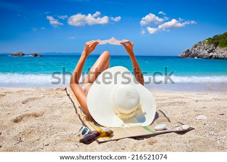 Beautiful woman reading book on Sarakiniko beach. Just 8km outside the village Parga after Agia village in Syvota area, Greece. - stock photo