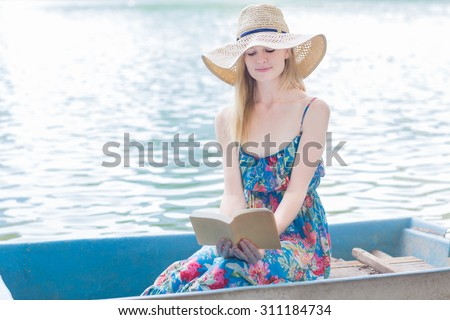 Beautiful woman reading on a rowboat   - stock photo