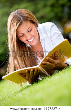 Beautiful woman reading outdoors looking very happy - stock photo