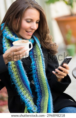 Beautiful woman reading text message holding coffee - stock photo
