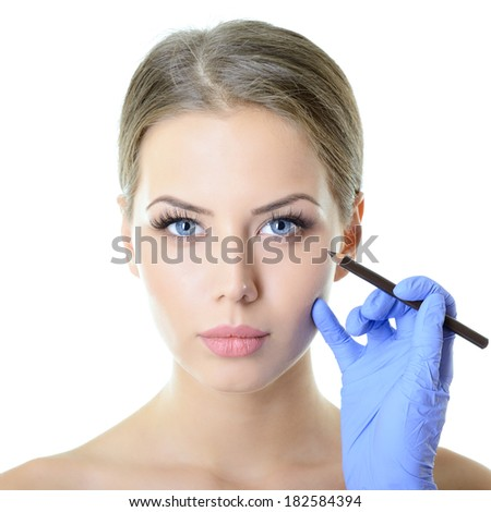Beautiful woman ready for cosmetic surgery, female face with doctor's hands with pencil, over white - stock photo