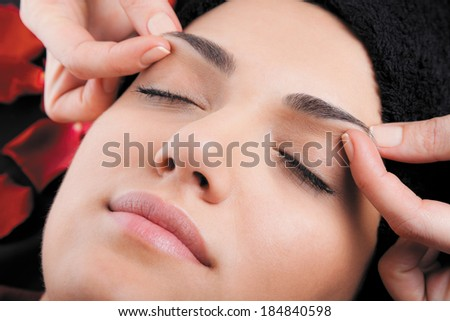 Beautiful woman receiving a facial massage lying on bed with rose petals. - stock photo