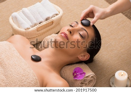 Beautiful Woman Receiving A Hot Stone Massage On Her Face In A Spa - stock photo