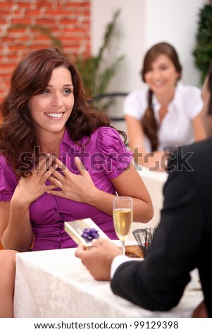 Beautiful woman receiving a small gift in a restaurant