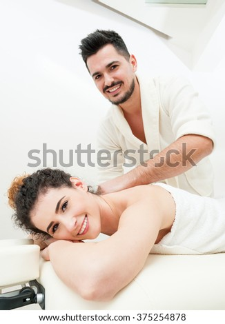Beautiful woman receiving and enjoying a relaxing massage by her boyfriend in spa salon - stock photo