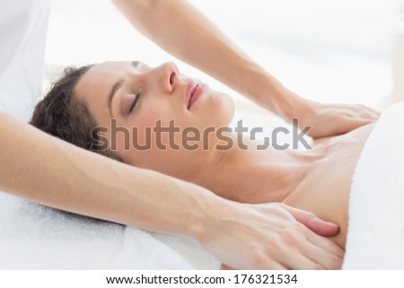 Beautiful woman receiving shoulder massage in health spa - stock photo