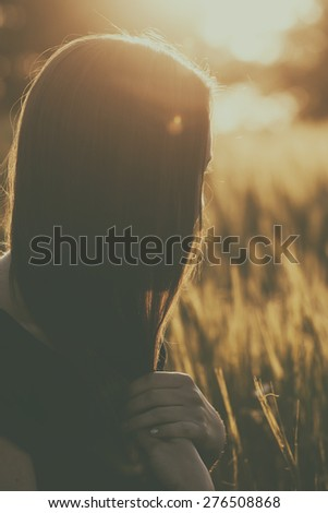 Beautiful woman relax on wheat field in sunset