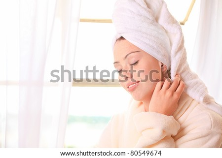 Beautiful woman relaxes by the window at a spa