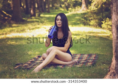 Beautiful woman relaxing and drinking water, sitting in  garden, on blanket