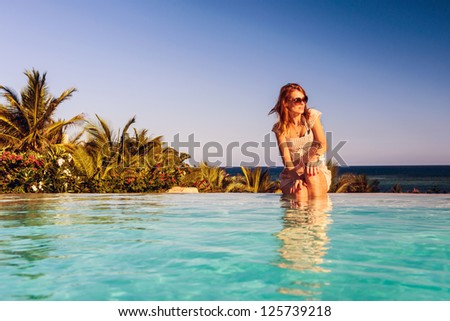 Beautiful woman relaxing at swimming pool - stock photo