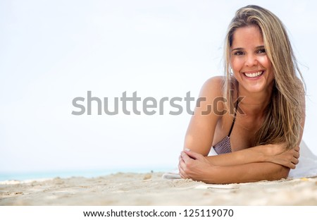 Beautiful woman relaxing at the beach and smiling - stock photo