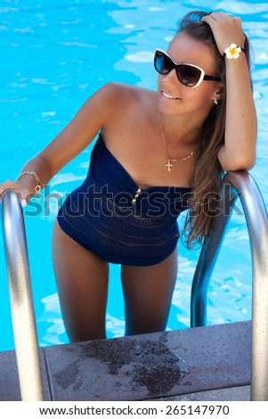 Beautiful woman relaxing at the luxury poolside, tanning. Girl at travel spa resort pool. Summer luxury vacation.  - stock photo