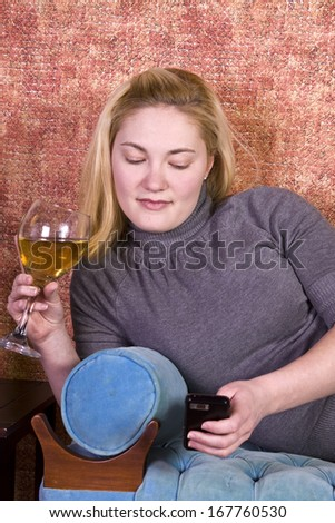 Beautiful Woman Relaxing byLaying on the Couch and Drinking Wine - stock photo