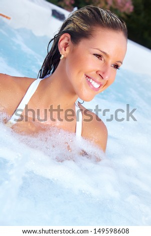 Beautiful woman relaxing in a hot tub. Vacation. - stock photo