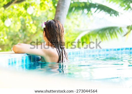 Beautiful woman relaxing in a pool at summer - stock photo