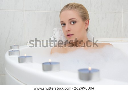beautiful woman relaxing in bath with candles - stock photo