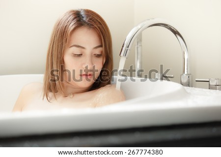 Beautiful woman relaxing in bathtub with water flow from faucet - stock photo