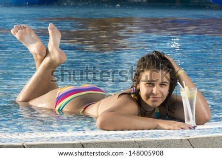 Beautiful woman relaxing in pool and drinking lemonade