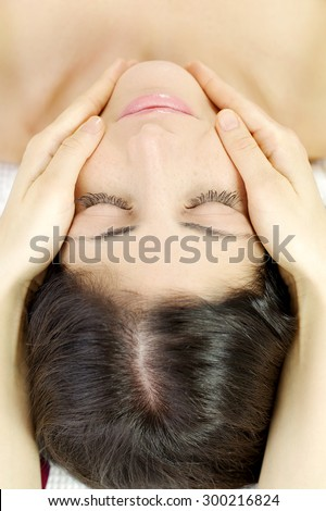 Beautiful woman relaxing in spa during face massage - stock photo