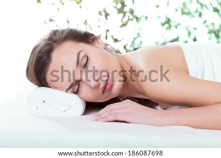 Beautiful woman relaxing in spa salon with eyes closed