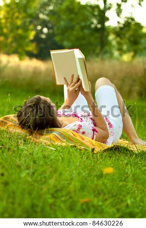 Beautiful woman relaxing in the park with a book. Vertical shot with copy space. - stock photo
