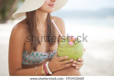 Beautiful woman relaxing on a paradise beach with coconut - stock photo