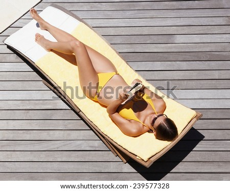 Beautiful woman relaxing on lounger in hotel - stock photo