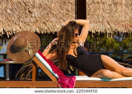 Beautiful woman relaxing on lounger in hotel, bali - stock photo