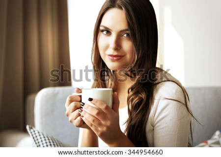 Beautiful woman relaxing on sofa in the room with cup of coffee