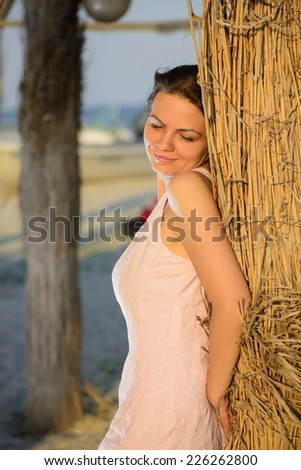 Beautiful woman relaxing on the beach on sunset. Portrait of a beautiful young woman on the beach. - stock photo