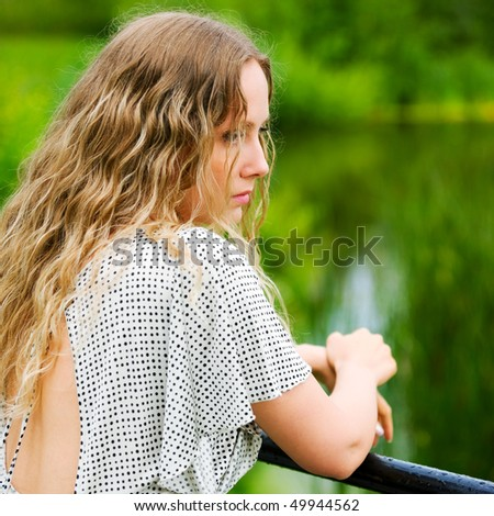 Beautiful woman relaxing on the shore of lake. - stock photo
