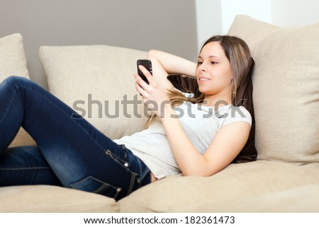 Beautiful woman relaxing on the sofa with her smartphone