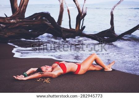 Beautiful Woman Relaxing on Tropical Beach at Sunset
