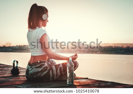 Beautiful woman relaxing outdoors after running workout.Yoga position towards sun