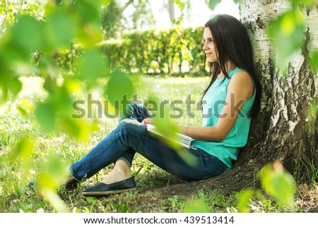 Beautiful woman relaxing outdoors on grass about tree.