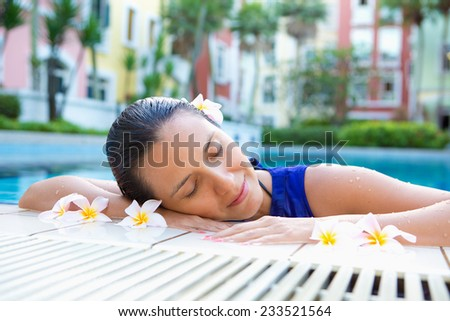 Beautiful woman relaxing with eyes closed by the side of swimming pool, flowers in hair - stock photo