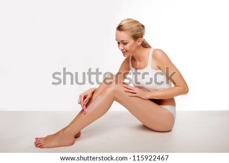 Beautiful woman removing her leg hair using a depilatory cream and applicator seated on the floor