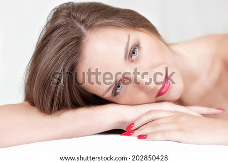 Beautiful woman resting head on hands in relaxed pose - stock photo