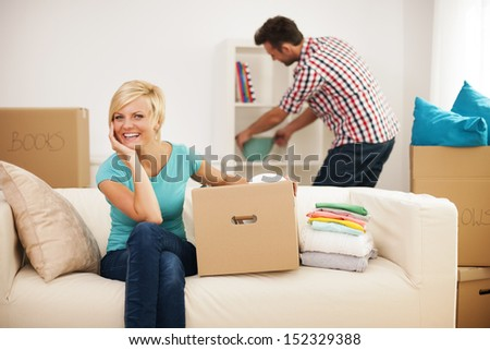 Beautiful woman resting on couch while her husband decorating their new living room - stock photo