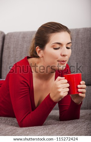 Beautiful woman resting on the sofa and drinking coffee