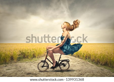 beautiful woman riding a bicycle - stock photo
