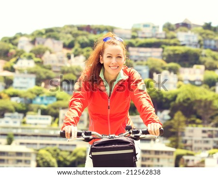 Beautiful woman riding on bike on summer sunny day outside, background of Sausalito town California USA. Outdoor activities, fun, vacation, travel concept. Positive face expressions, emotions, feeling - stock photo