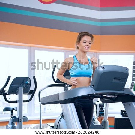beautiful woman runs on a treadmill - stock photo