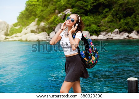 Beautiful woman's body in sexy summer  travel outfit over beach background.Casual style with beauty accessories.High fashion urban style.floral big travel bag, summer vintage outfit,street style,music - stock photo