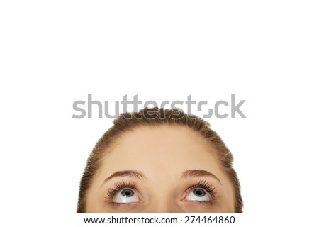 Beautiful woman's eyes looking up on space.