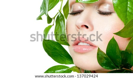 beautiful woman's face, surrounded by green leaves - stock photo